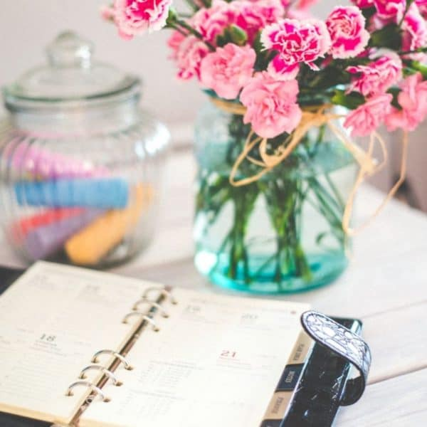 Work diary on a desk next to a vase of flowers