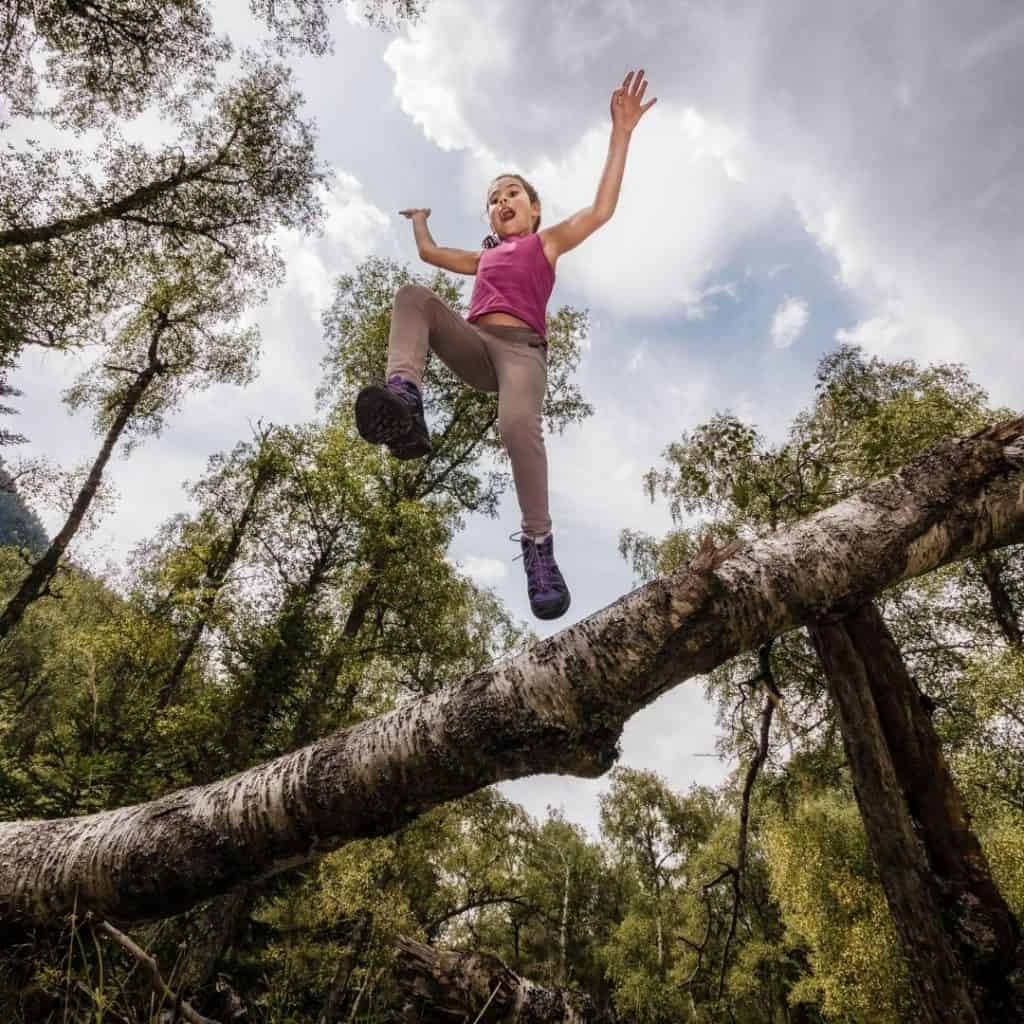A child leaping over a branch